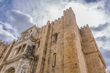 View Of Lateral Facade Of The Gothic Building Of Coimbra Cathedral, Coimbra City And Sky As Background, Portugal