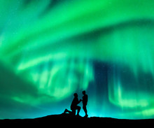 Aurora Borealis And Silhouette Of A Man Making Marriage Proposal To His Girlfriend. Night Landscape With Northern Lights, Starry Sky And Lovers. Couple, Relationship. Aurora With People. Polar Lights