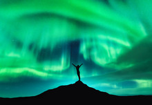 Aurora Borealis And Silhouette Of A Woman With Raised Up Arms On The Mountain Peak. Lofoten Islands, Norway. Aurora And Happy Girl. Starry Sky And Polar Lights. Night Landscape With Aurora And People