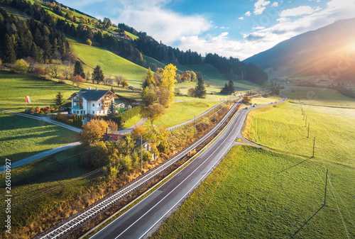 Montage in der Fensternische Melone Aerial view of the road in mountain valley at sunset in summer in Dolomites, Italy. Top view of cars on asphalt roadway, house, railroad, hills with green meadows, blue sky, trees, buildings. Highway
