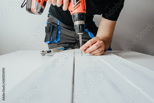 Obraz A man screwing a screw into a wooden board. The concept of DIY and renovation of new things. A man tinkering at home, working with wood. - fototapety do salonu