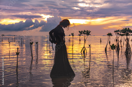 Montage in der Fensternische Lavendel young woman standing in water at sunset silhouette
