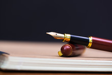 Close Up Of Fountain Pen Or Ink Pen With Notebook Paper On Wooden Working Table With Copy Space, Office Desk Concept. Shallow Focus.