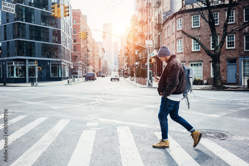 Man wearing hat and jacket walking on the city crossroad with mobile phone in ha Fototapete