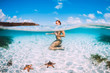 Leinwandbild Motiv Naked woman swim in blue ocean with starfish, underwater in tropical sea