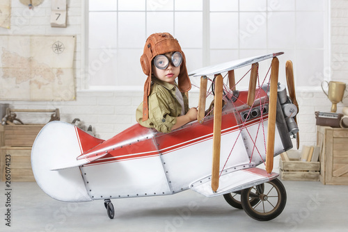 Photo Little boy in the guise of a pilot at the helm of a toy-airplane
