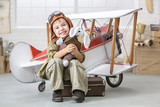 Fototapeta Panels - Little boy in the image of the pilot near the toy-plane