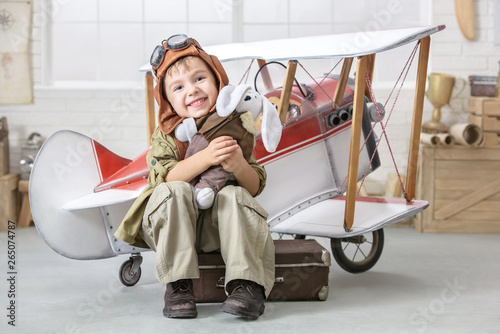 Little boy in the image of the pilot near the toy-plane