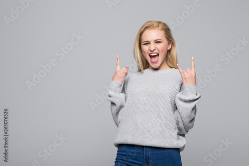 Valokuva  Happy girl in gray sweater with her fists up, isolated on gray background