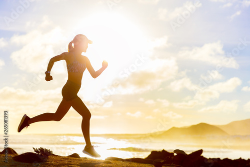 Fototapety, obrazy: Summer workout athlete runner girl trail running on summer beach. Fit body silhouette of sports Woman in sportswear cap sprinting motion in outdoors nature training cardio with jogging exercise.