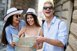 Happy group of tourists traveling and sightseeing together at summer
