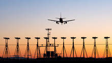 Sunset Over An International Airport With The Silhouette Of A Passenger Airplane Landing On A Runway.