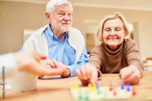Rentner Paar hat Spaß beim Brettspiel Fototapete