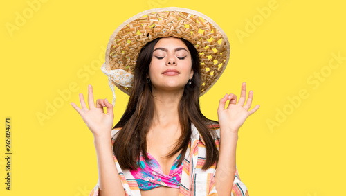 Papiers peints Individuel Teenager girl on summer vacation in zen pose over isolated yellow background