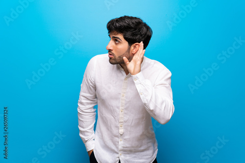 Fotografia  Young man over isolated blue wall listening to something by putting hand on the