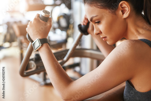 Perfect training. Side view of conentrated young woman with smart watch on her hand exercising at gym
