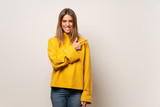 Woman with yellow sweater over isolated wall pointing to the side to present a product - 265103914