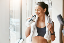 Time For Rest. Young And Cheerful Woman In Sportswear With White Towel On Her Shoulders Drinking Water While Standing In Front Of Windows At Gym