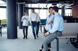 Taking their business on the move. Full length of young modern people in smart casual wear having a discussion while walking through the large modern office.