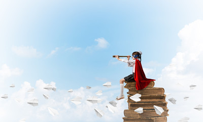 Girl power concept with cute kid guardian against cloudscape background