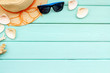 Leinwanddruck Bild - Summer travaling to the sea with straw hat, sun glasses, shells on mint green wooden background top view mock up