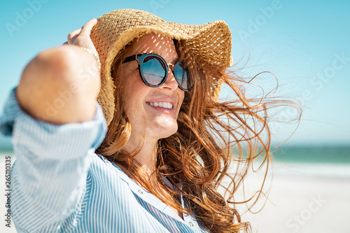 Foto Mature woman with beach hat and sunglasses