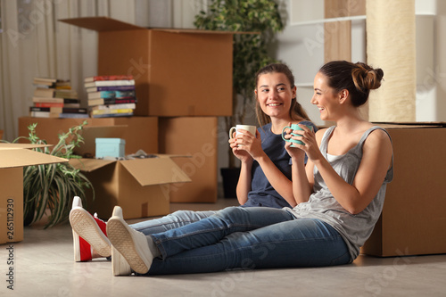 Fotografie, Obraz Happy roommates moving home resting and talking