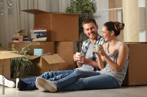 Happy couple moving home resting and talking Canvas Print