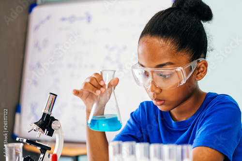 Valokuva  Young African American mixed kid testing chemistry lab experiment and shaking gl