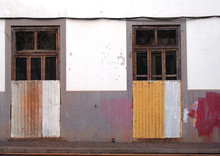 The Front Of A White And Grey Painted Abandoned House With Broken Doors And Windows Boarded Up With Rusty Corrugated Iron With Splashed Of Red And Yellow