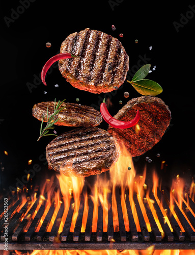Fototapeta Beef milled meat on hamburger with spices fly over the flaming grill barbecue fire. obraz