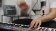 Musician having wrist pain while playing midi keyboard in home music studio.