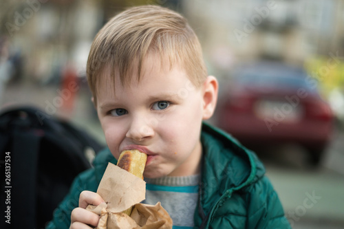 Valokuva  A little hungry boy is eating a loaf on the street.