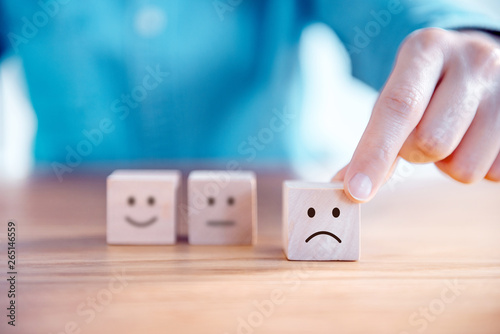 Fotografía Close up customer hand choose sad face and blurred smiley face icon on wood cube, Service rating, satisfaction concept