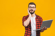 Portrait of amazed man holding laptop computer and looking at camera over yellow background.