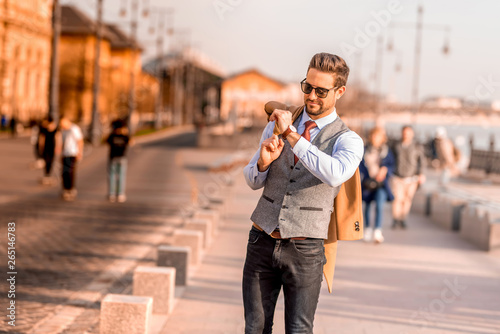 Fotomural  An elegant man walking on the streets and checking the time