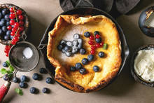 Fresh Baked Dutch Baby Pancake In Iron Cast Pan Served With Blackberry And Red Currant Berries, Mascarpone Cheese, Sugar Powder, Jug Of Cream, Vintage Sieve Over Beige Background. Flat Lay, Close Up