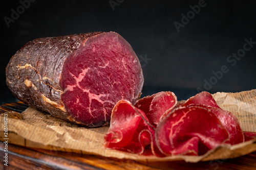 Half a smoked bresaola and cut pieces on a chopping Board. Italian Antipasti, rustic style - 265148713