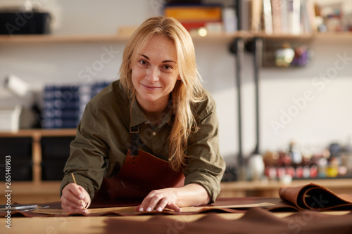 Obraz Portrait of female artisan smiling at camera while working with leather in workshop, copy space - fototapety do salonu