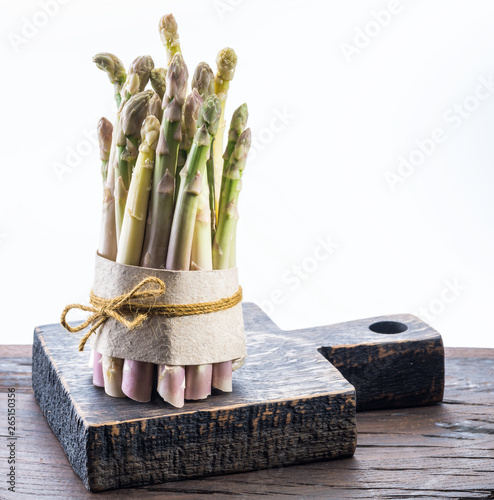 Photo Bundle of cultivated white asparagus on wooden board.