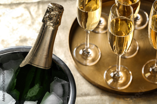 Bottle of champagne in bucket with ice and glasses on table, closeup Fototapeta