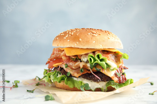 Fototapeta Tasty burger with bacon on table against color background obraz