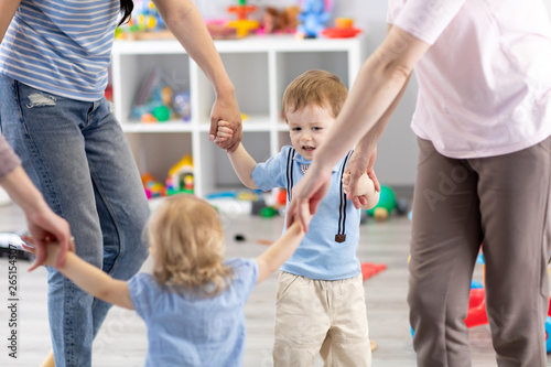 Fotografia Little children and mothers roundelay in daycare