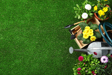 Flat Lay Composition With Gardening Equipment And Flowers On Green Grass, Space For Text