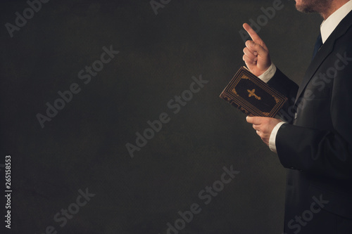 Photo  A standing man in Suit with a Bible and a wagging finger