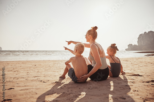 Mother and children sitting on a beach enjoying the seaview