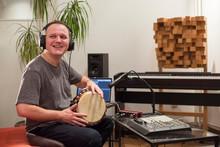 Musician Playing Djembe Drum Instrument In Home Music Studio.