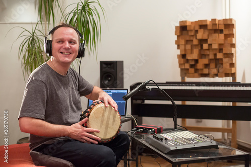 Obraz na plátne Musician playing djembe drum instrument in home music studio.