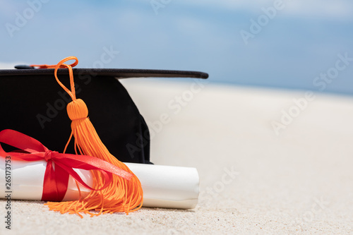Fotografija  Close up Graduation cap and certificated on the beach with beautiful sea in summ