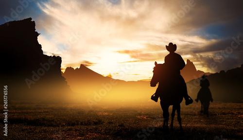 Fototapeta Cowboys on horseback at sunset obraz